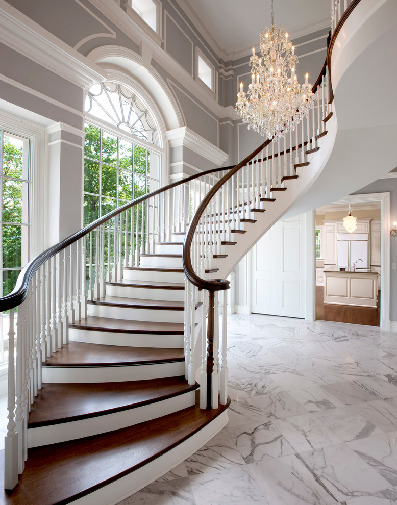 Staircase - traditional wooden curved wood railing staircase idea in Milwaukee with painted risers