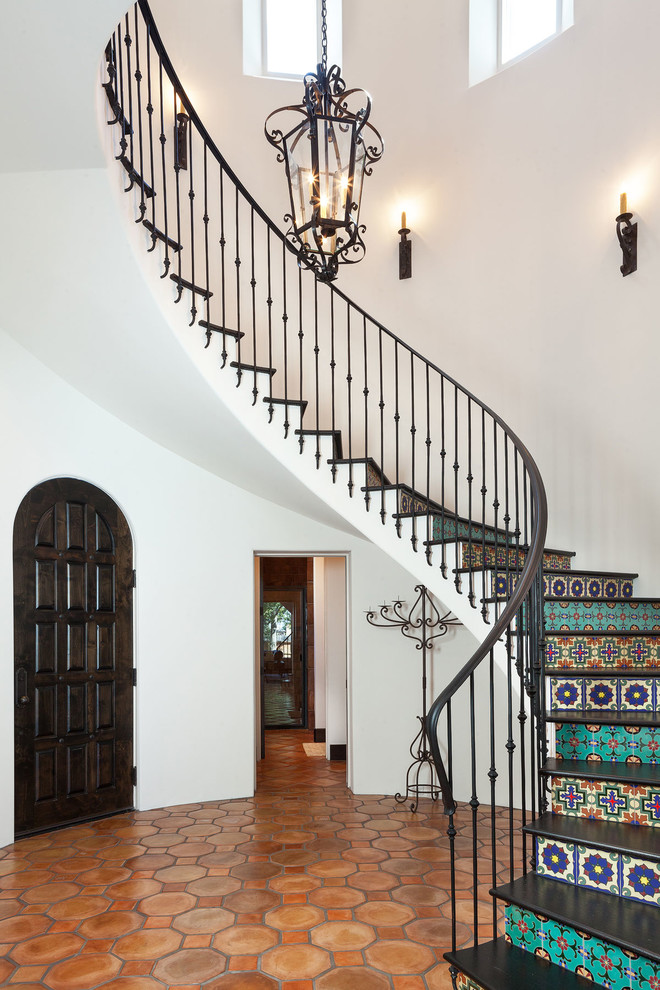 Tuscan curved metal railing staircase photo in Houston with tile risers