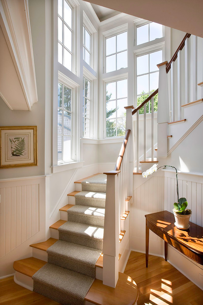 Example of a large ornate wooden curved staircase design in Boston with painted risers