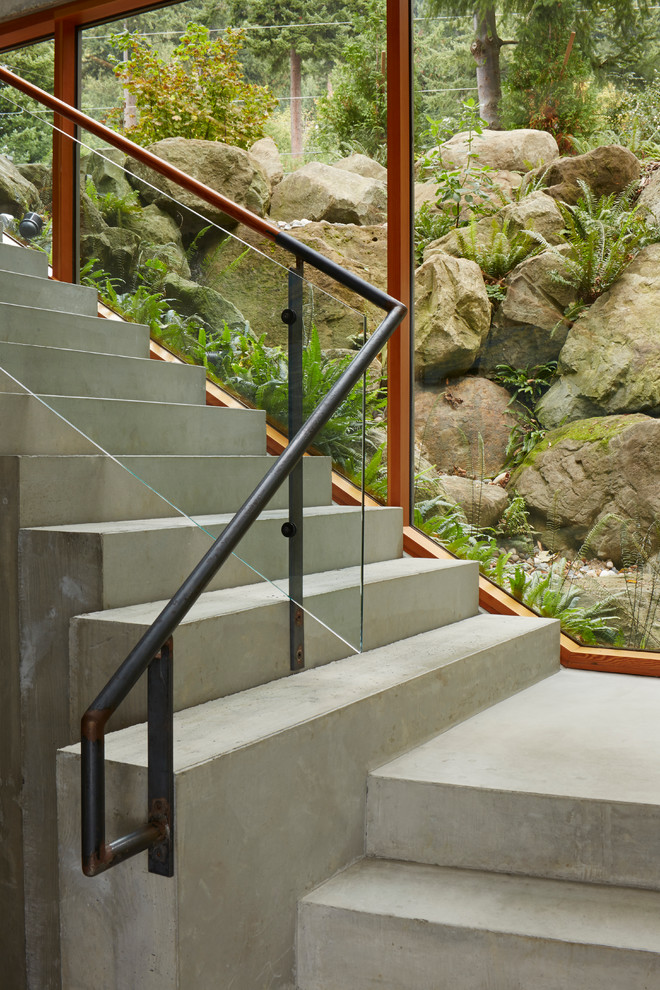 Staircase - contemporary concrete l-shaped glass railing staircase idea in Seattle with concrete risers