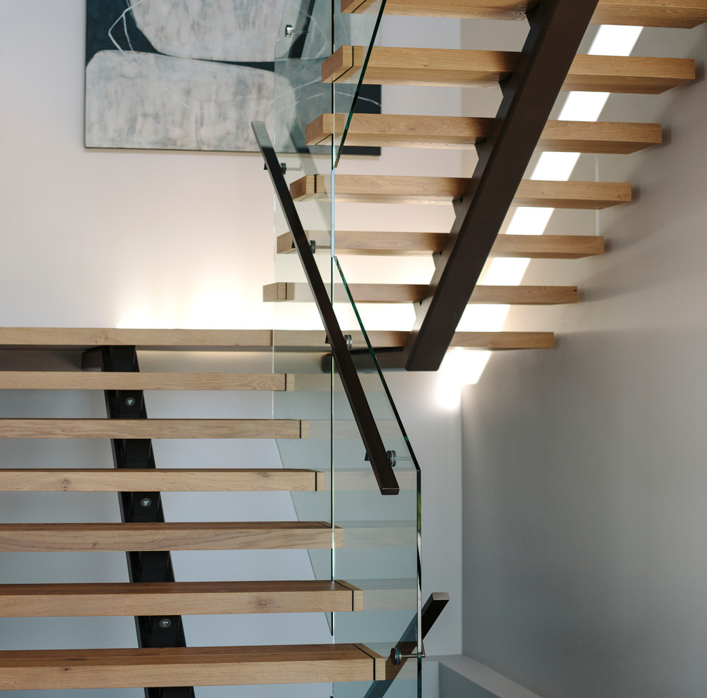 Inspiration for a mid-sized contemporary wooden u-shaped metal railing staircase remodel in Vancouver with wooden risers