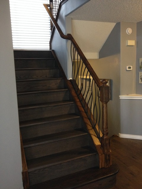 bent iron design interior railing with a distressed wood handrail and