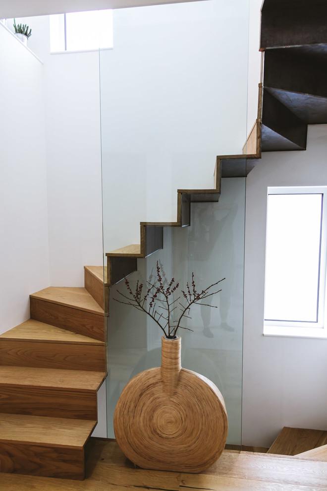 Ispirazione per una scala curva contemporanea con pedata in legno, alzata in legno e parapetto in vetro