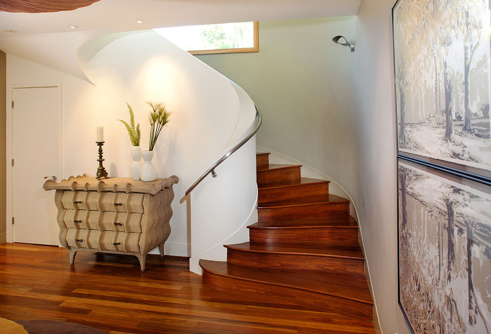 Staircase - mid-sized contemporary wooden curved metal railing staircase idea in San Francisco with wooden risers