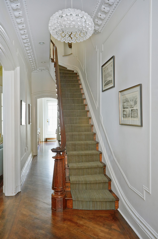 Staircase - transitional wooden curved staircase idea in New York with wooden risers