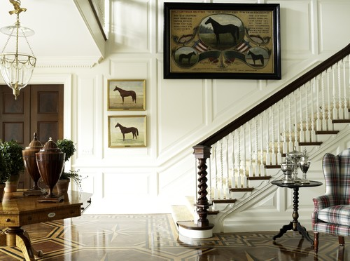 white traditional staircase with wood floor and inlaid design and millwork on the stair wall with oversize art of horses