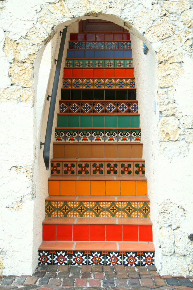 Staircase - eclectic terra-cotta straight staircase idea in Miami with tile risers
