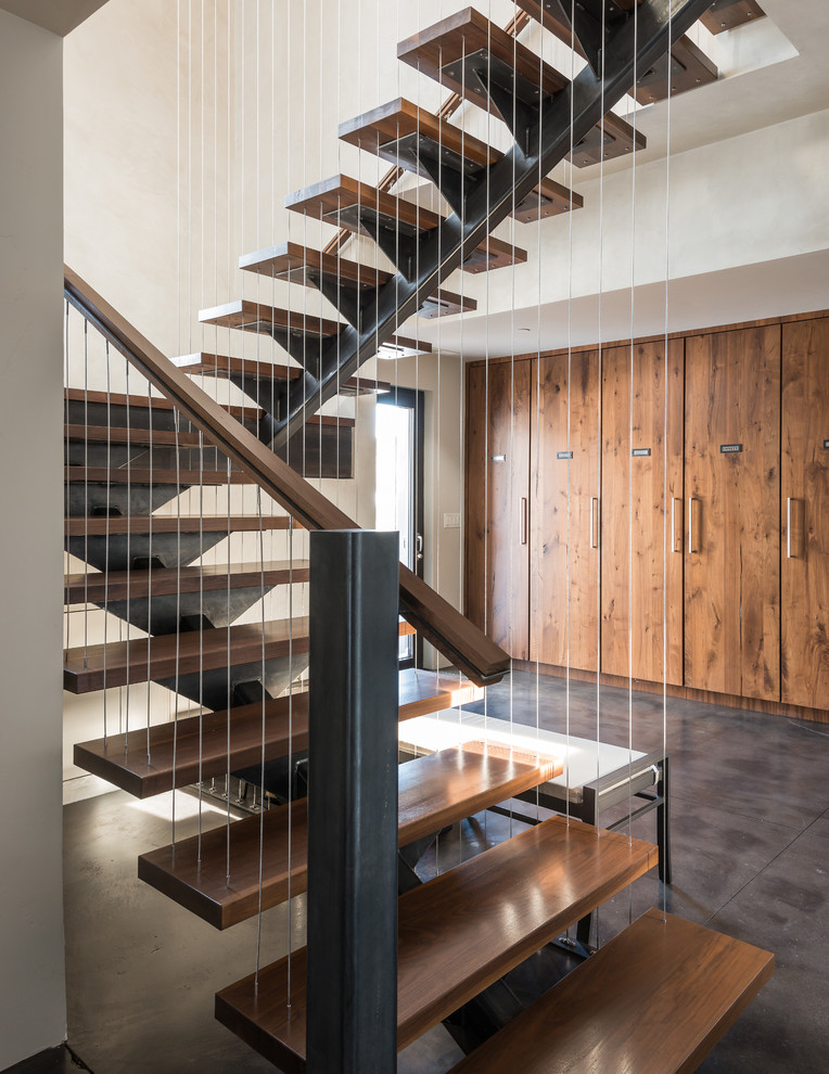 Example of a trendy wooden open and cable railing staircase design in Other