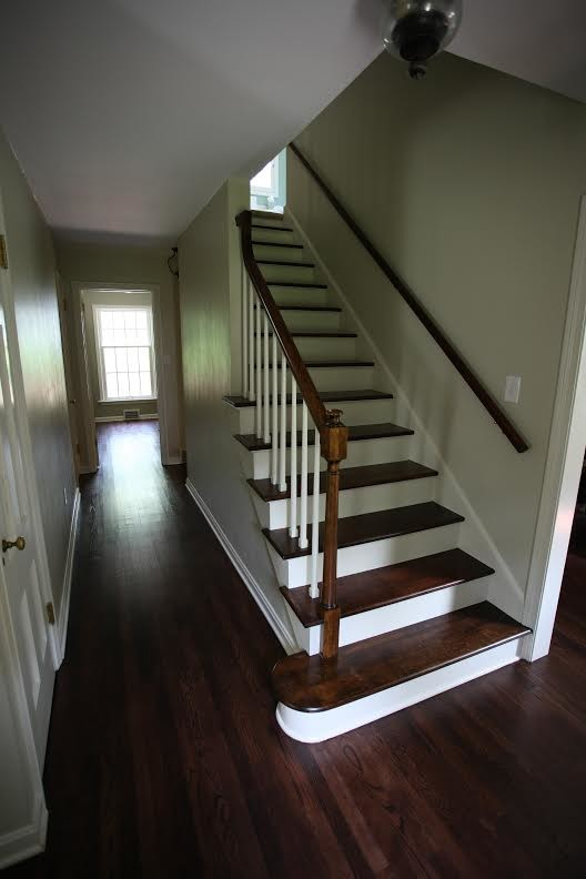 Mid-sized elegant wooden straight staircase photo in Cleveland with painted risers