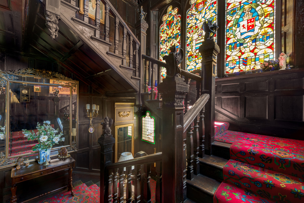 Example of a huge ornate carpeted l-shaped staircase design in Devon with wooden risers