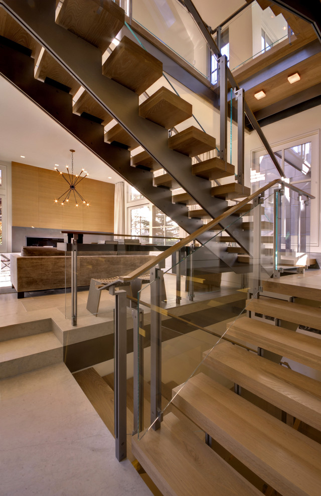 Example of a trendy open and glass railing staircase design in Denver