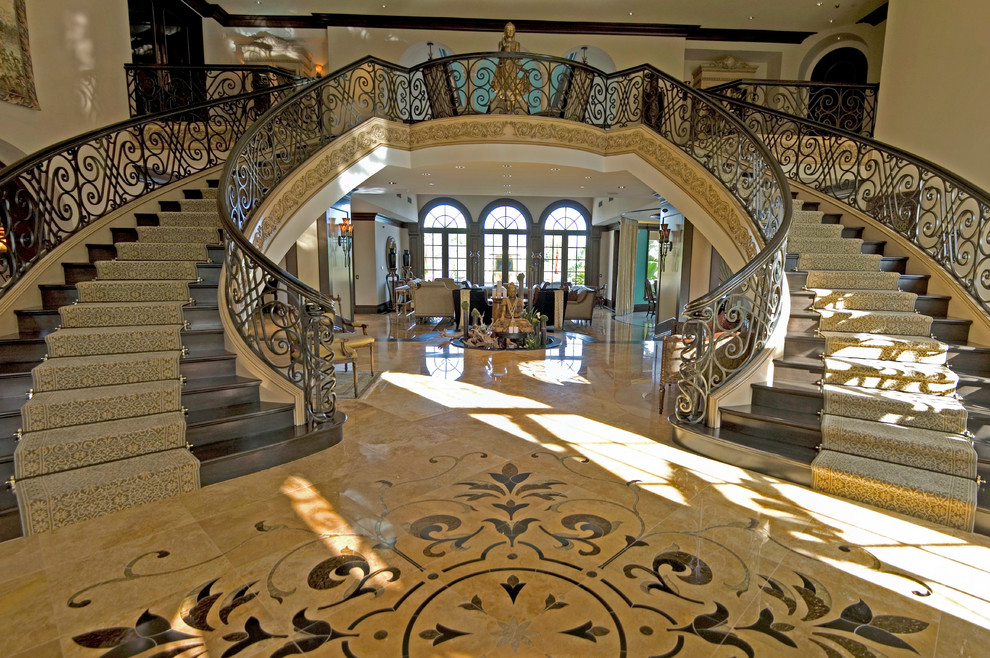 Huge elegant wooden curved staircase photo in Los Angeles