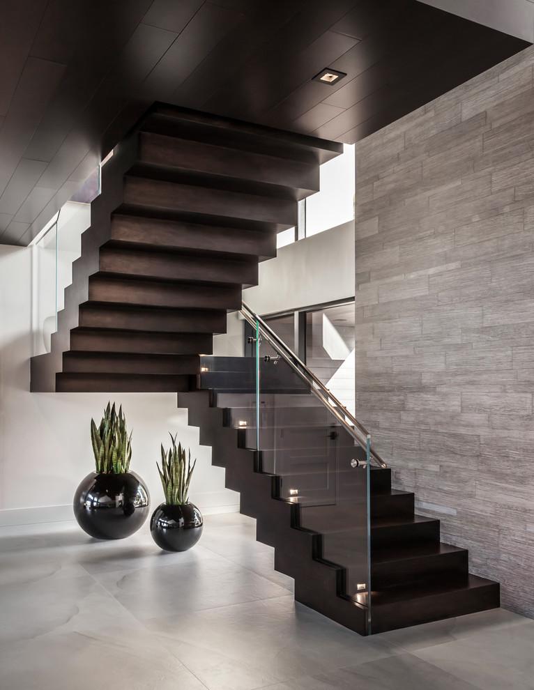 """Esempio di una grande scala a """"U"""" contemporanea con pedata in legno, alzata in legno e parapetto in vetro"""