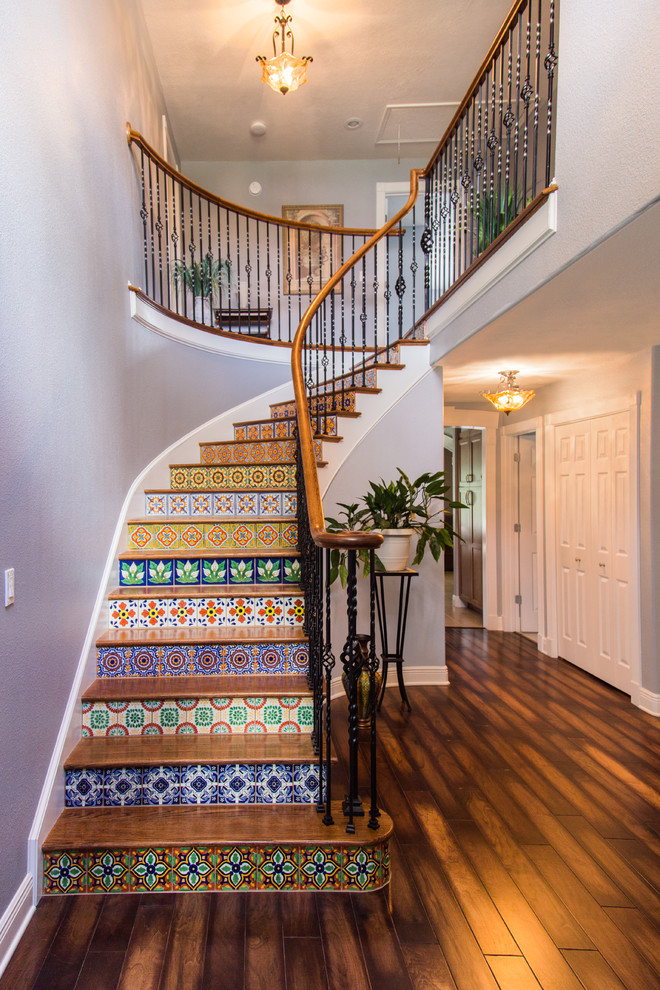 Example of a large tuscan wooden curved staircase design in Tampa with tile risers