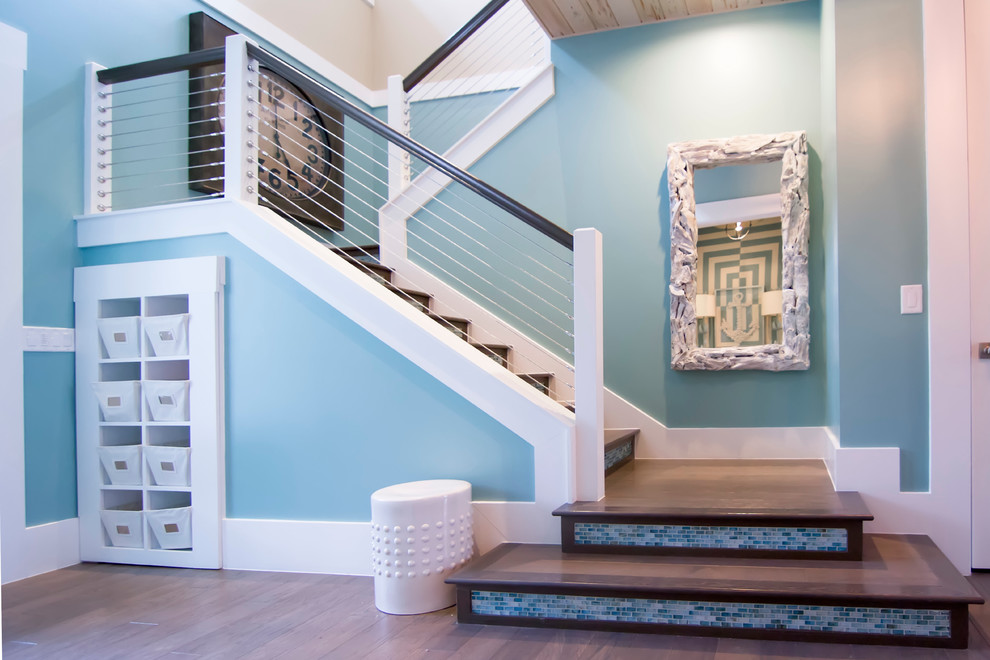Large island style wooden u-shaped cable railing staircase photo in Jacksonville with tile risers