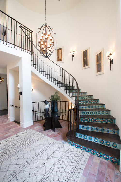 Spanish style foyer with brick flooring and blue tiled stair risers and curved iron staircase