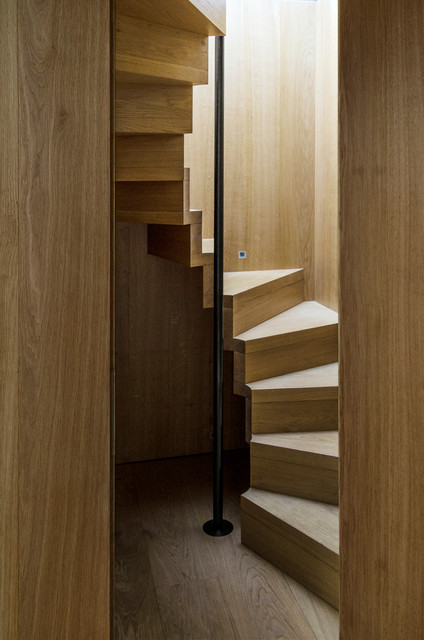 Example of a trendy wooden curved staircase design in London with wooden risers