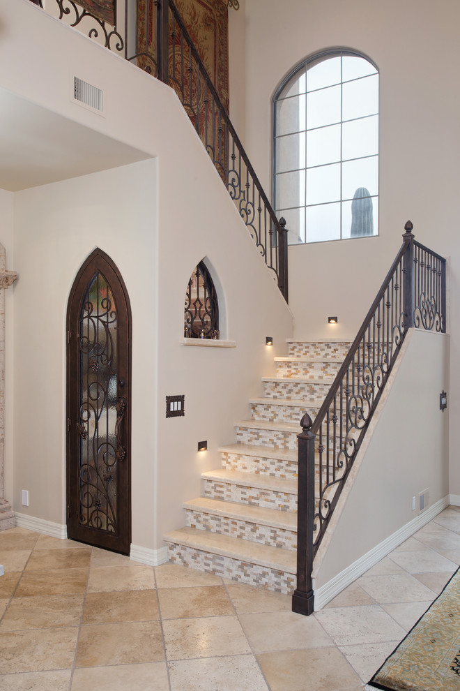 Mid-sized tuscan travertine u-shaped metal railing staircase photo in Phoenix with tile risers