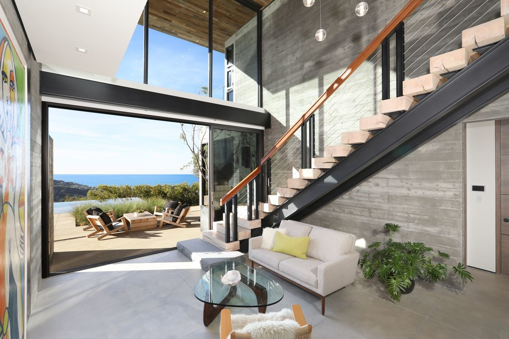 Example of a trendy wooden l-shaped cable railing staircase design in Orange County with wooden risers