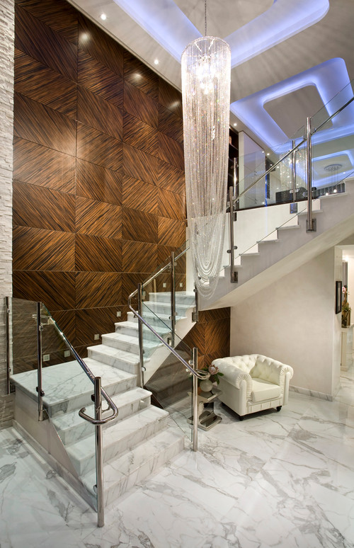 Modern foyer with glass and chrome staircase and marble floor and wood panels on the staircase wall