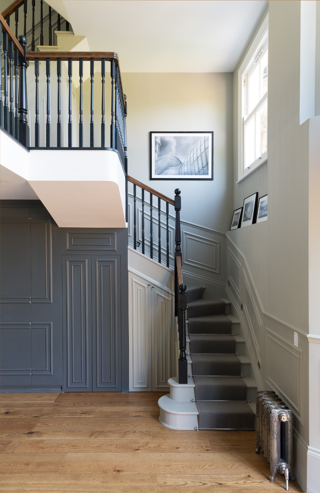 Ornate painted curved staircase photo in London with painted risers