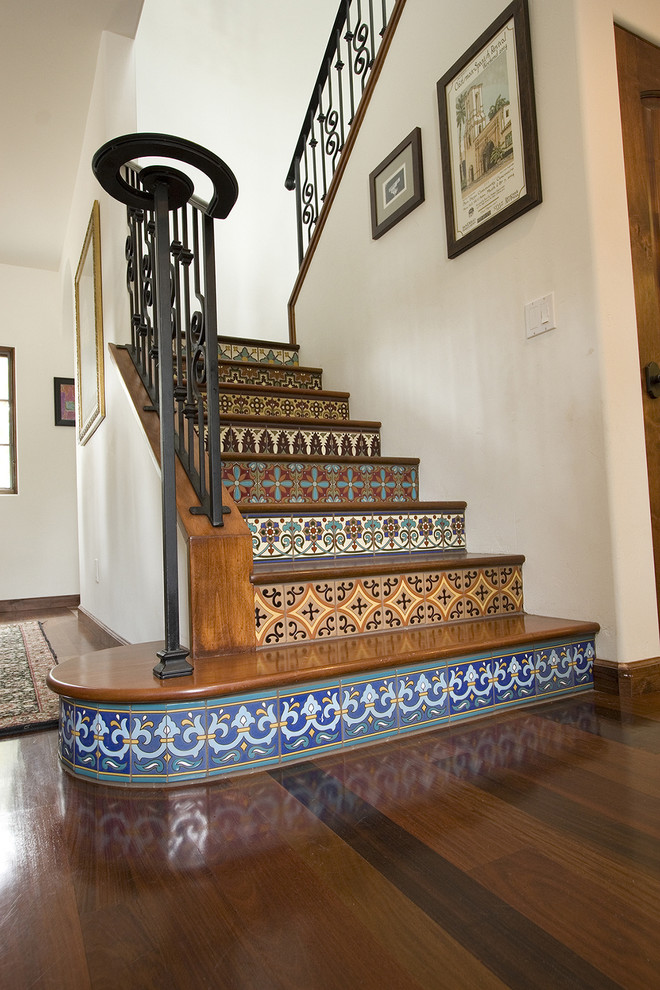Example of a tuscan wooden staircase design in Los Angeles with tile risers
