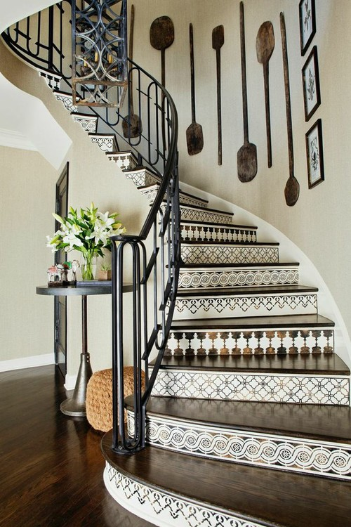 Curved staircase with iron railing and patterned tile stair riser and collection of antique bread paddles hanging on the wall