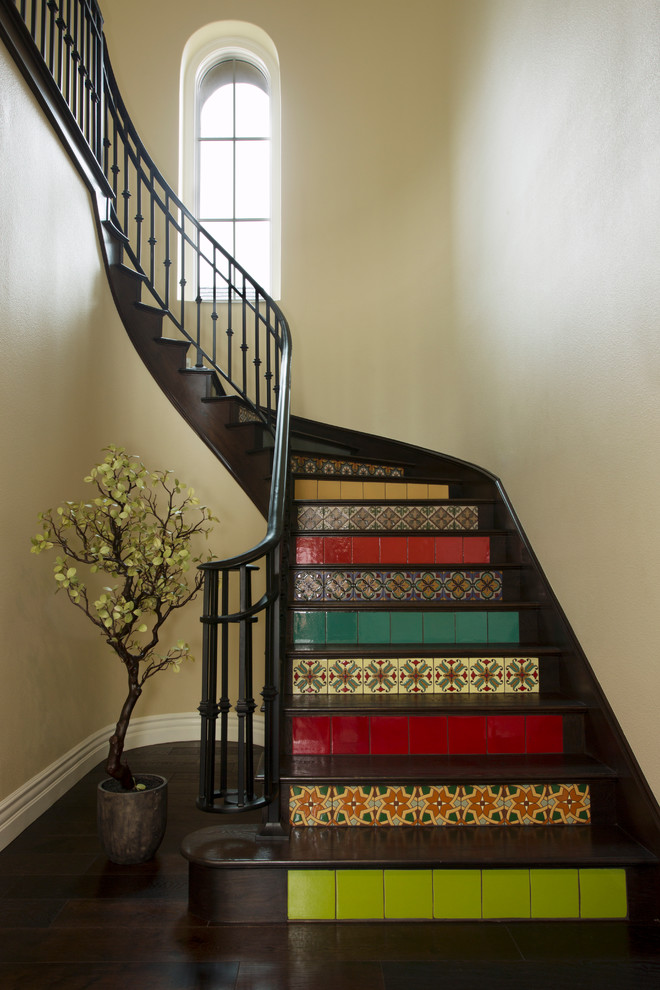 Staircase - mediterranean wooden curved staircase idea in San Francisco with tile risers