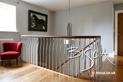 Inspiration for a mid-sized modern wooden curved staircase remodel in Other with wooden risers