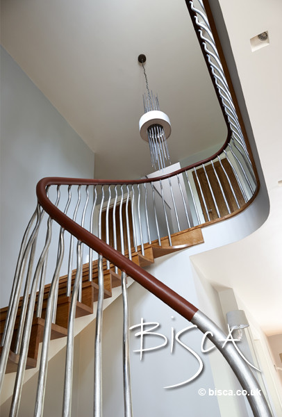 Mid-sized minimalist wooden curved staircase photo in London with wooden risers