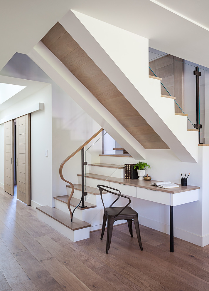 Huge trendy wooden u-shaped glass railing staircase photo in San Francisco with painted risers