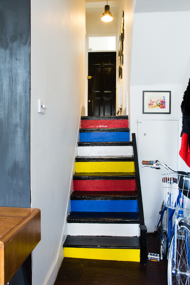 Inspiration for an eclectic painted staircase remodel in London with painted risers