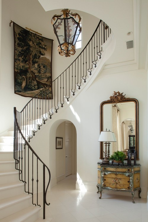 foyer  with white tiled floor and curved iron staircase and large tapestry hanging on staircase wall