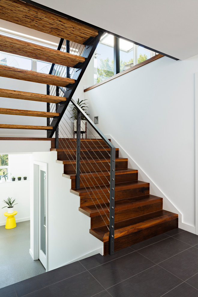 Staircase - contemporary wooden u-shaped cable railing staircase idea in Seattle with wooden risers