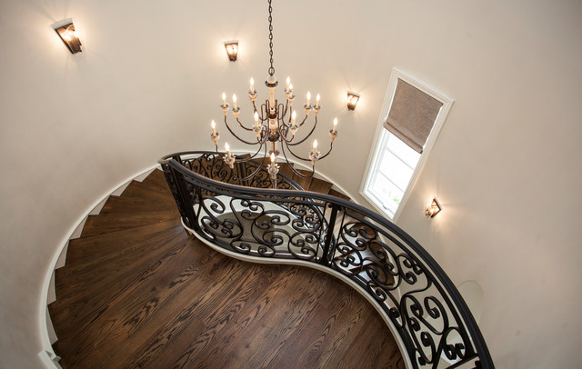 Large tuscan wooden curved metal railing staircase photo in Other with wooden risers