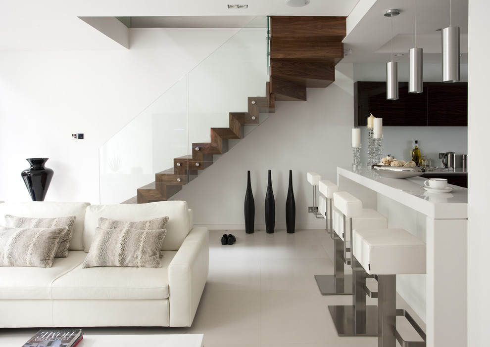 Minimalist wooden floating glass railing staircase photo in London with wooden risers