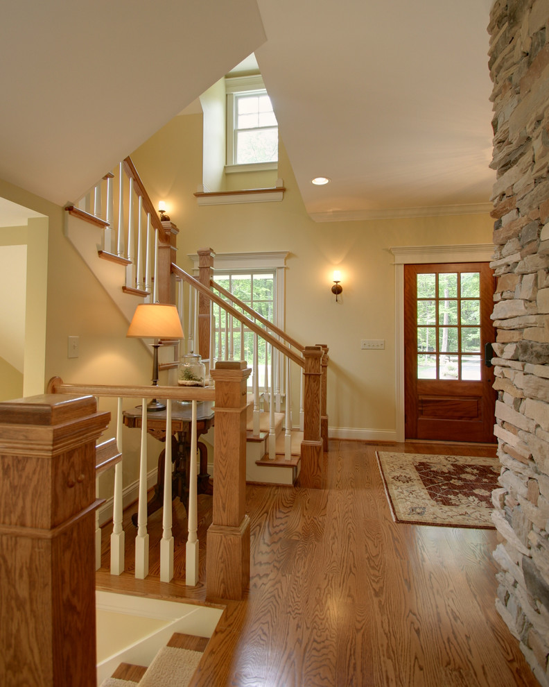 Example of a classic wooden wood railing staircase design in Columbus