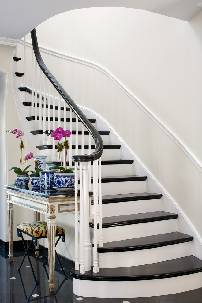 Staircase - traditional curved staircase idea in Chicago with painted risers