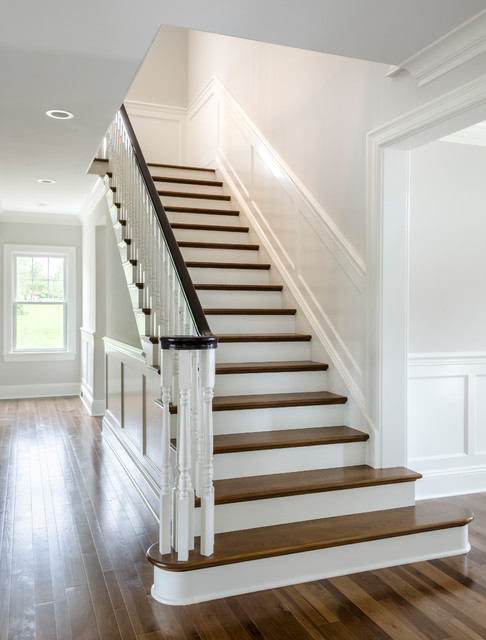 Mid-sized elegant wooden u-shaped wood railing staircase photo in Cleveland with painted risers