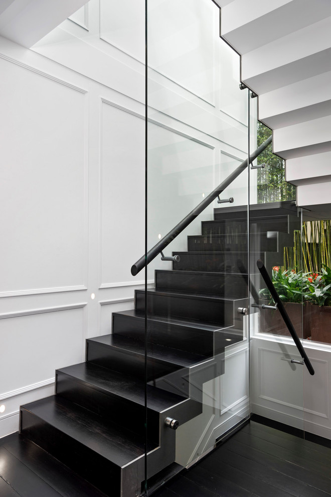 Design ideas for a contemporary u-shaped staircase in Sydney with glass railing and panelled walls.