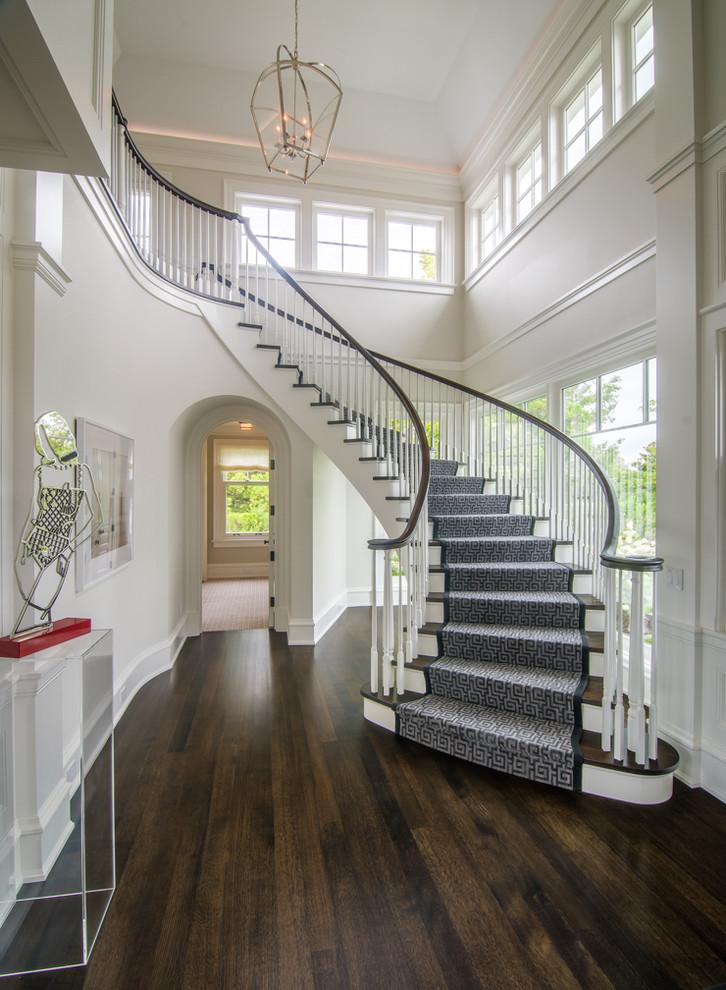 Foto de escalera curva, tradicional renovada, con escalones de madera, contrahuellas de madera y barandilla de madera