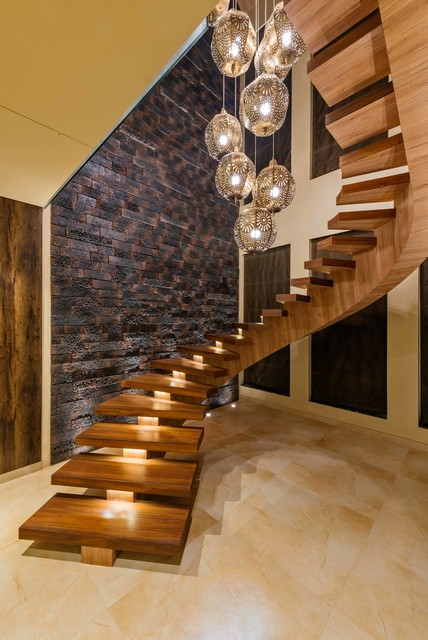Inspiration for a large contemporary wooden curved open staircase remodel in Mumbai