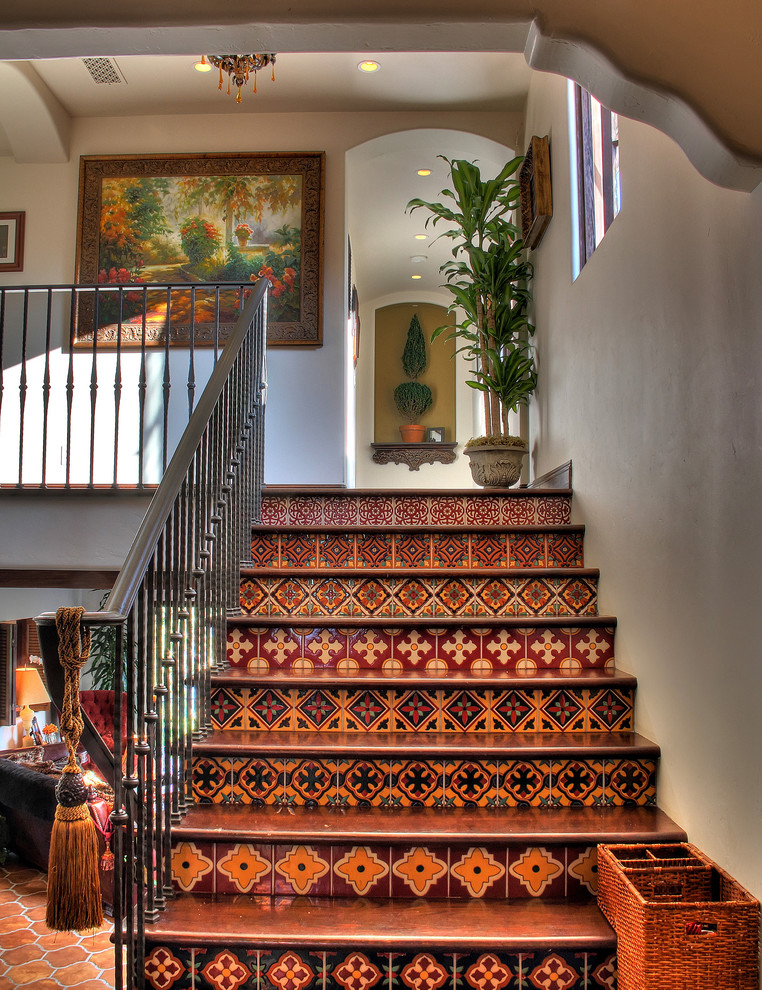 Staircase - southwestern wooden metal railing staircase idea in Los Angeles with tile risers