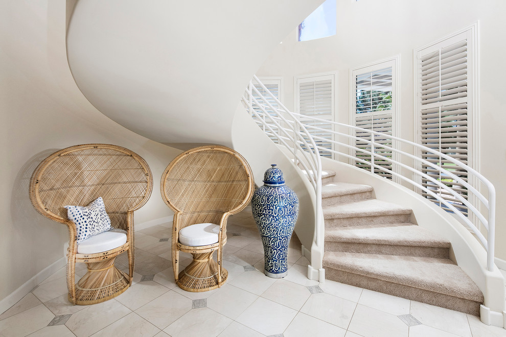 Inspiration for a coastal carpeted spiral staircase remodel in Los Angeles with carpeted risers