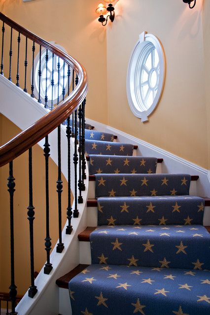 Elegant carpeted spiral staircase photo in New York with wooden risers