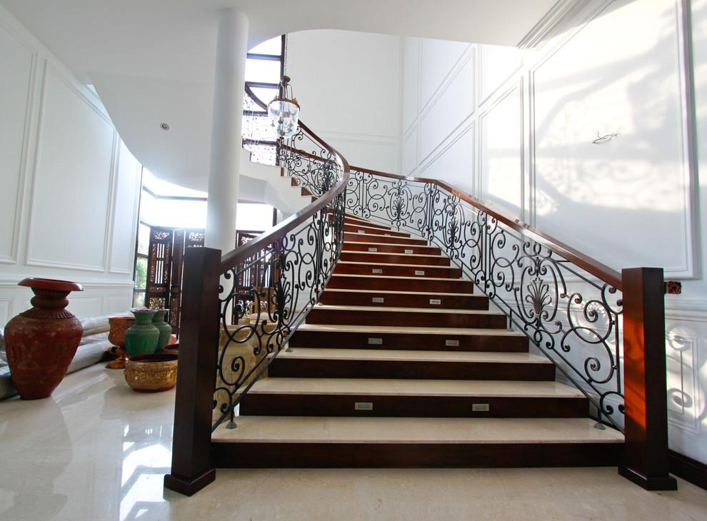 Immagine di una scala curva mediterranea con pedata in travertino, alzata in legno e parapetto in metallo