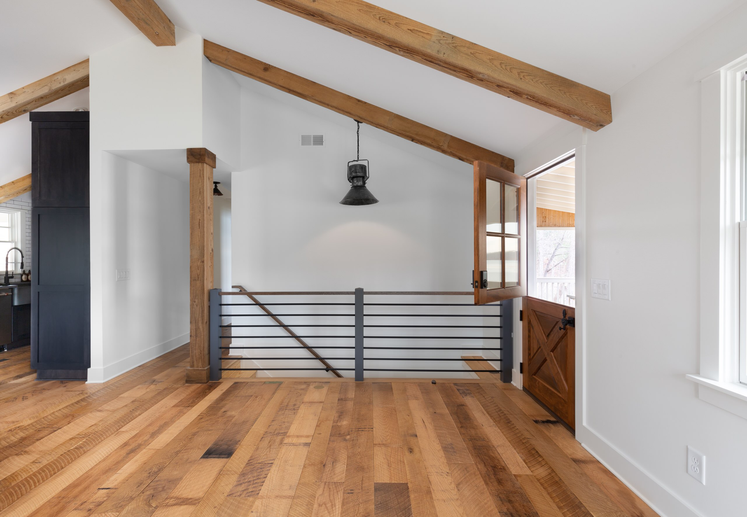 Stair case detail with antique industrial factory pendant light and Dutch door o