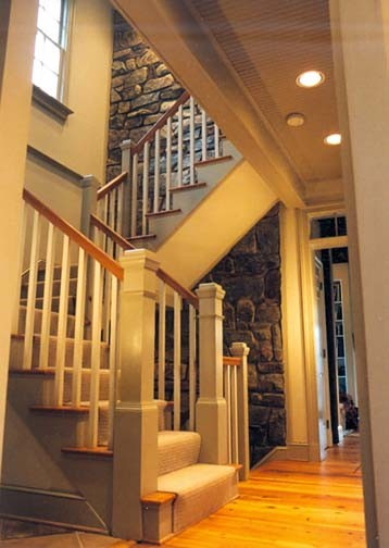 stair hall that follows an interior stone wall traditional staircase