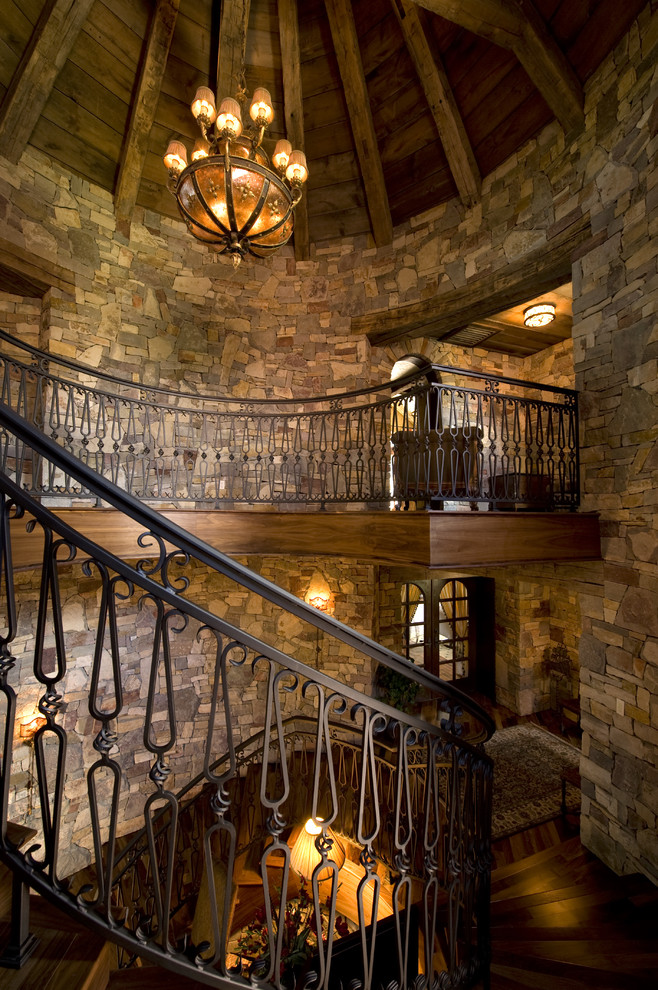 Staircase - rustic wooden curved staircase idea in Minneapolis