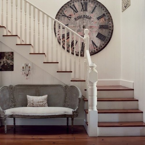 white staircase with gray  french settee at the bottom and oversized antique clock on the first landing